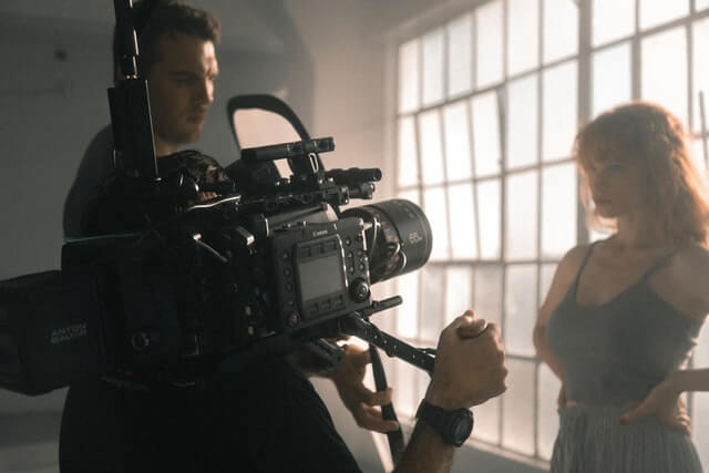 A man holding a large Canon camera and pointing it at a woman stood by a window.