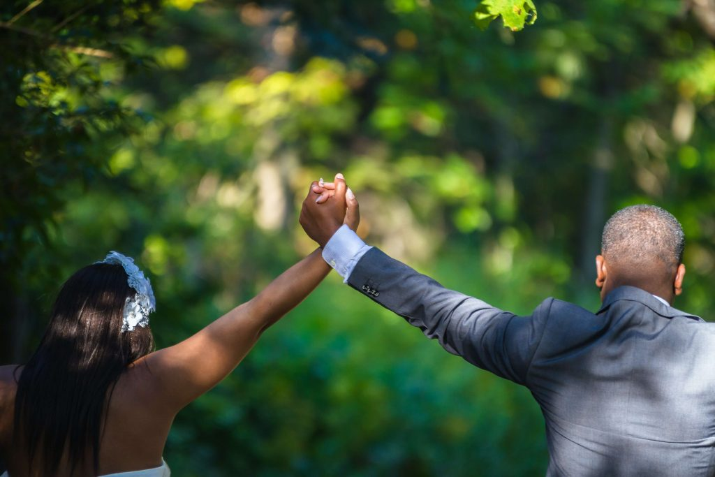A bride and groom holding hands in the air.