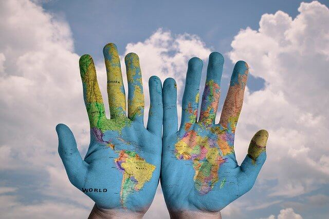 Two hands covered in a world map.