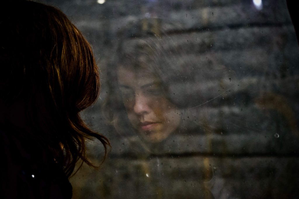 Woman with brown hair looking out window.